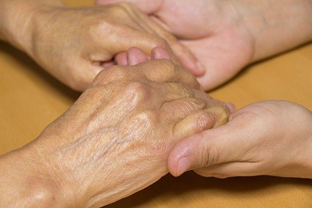 高齢者の手を支えるあたたかな手