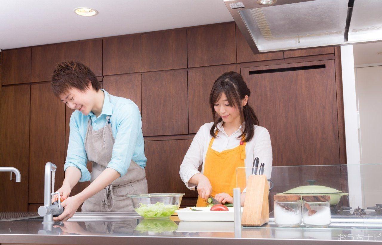 キッチンで料理をする共働きの夫婦