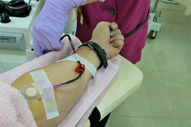 献血をする男性の左手