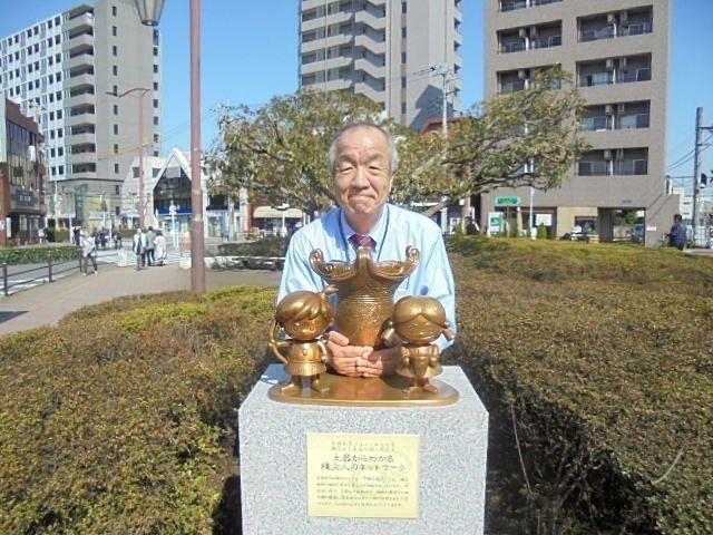 東伏見駅北口ロータリーにある下野谷遺跡のモニュメントと写真を撮る鈴木義晴