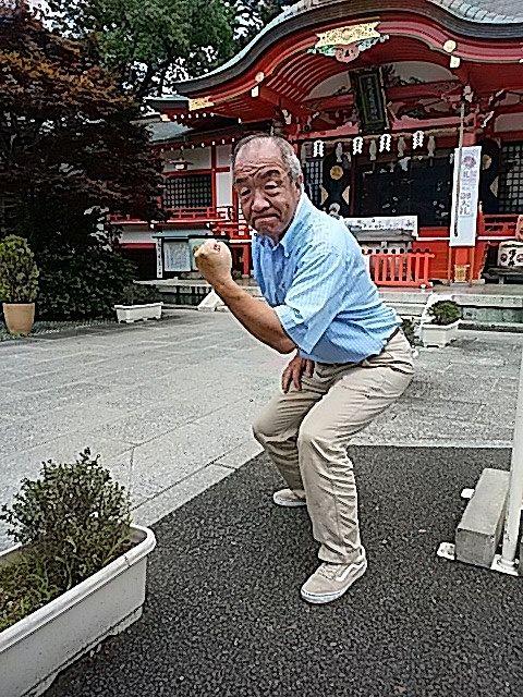 東伏見稲荷神社をバックに顔晴るポーズをする鈴木義晴