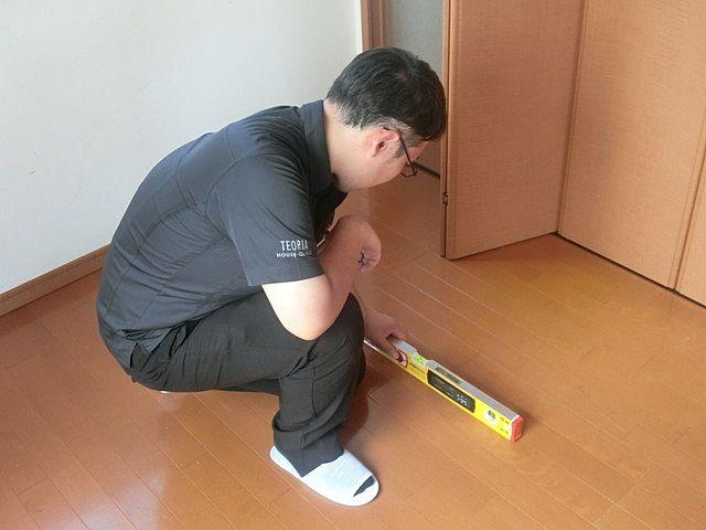 建物診断で床の傾きを確認している様子