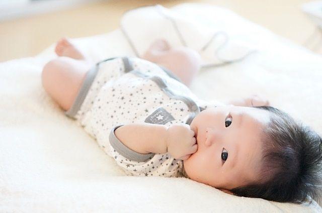 指を加えてママを見る赤ちゃん