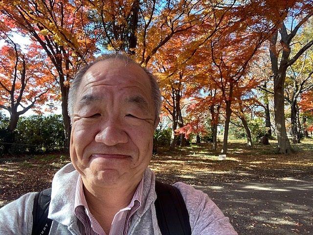 西東京市にある東大農場にて紅葉をバックに写真を撮るスプラッシュの鈴木義晴