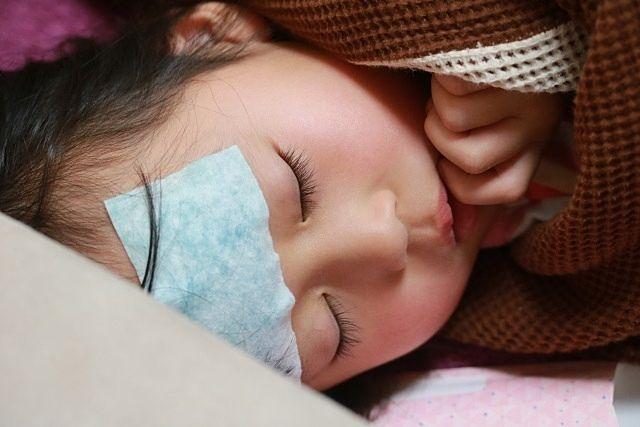 インフルエンザが発症しおでこに冷えピタを貼り寝込む女の子(2019,12,24)スプラッシュ