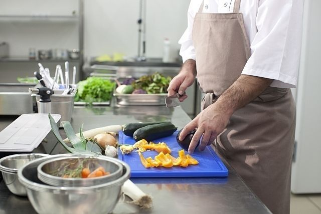 男性の料理教室で野菜を切る人のイメージ写真です