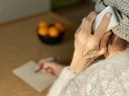 自宅にかかってきた電話を受けながらメモをとる高齢者 スプラッシュ