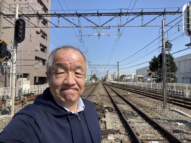 西武新宿線「東伏見」駅の踏切で自撮りする代表の鈴木義晴