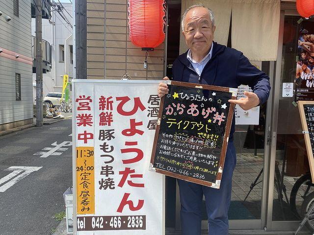 ひょうたんの店先で撮影する鈴木