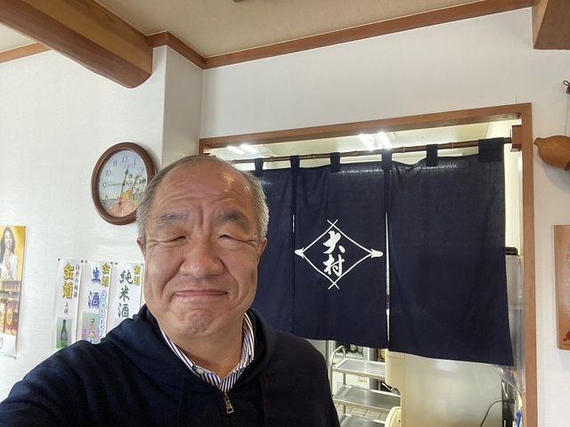 そば処大村の暖簾をバックに撮影する鈴木義晴