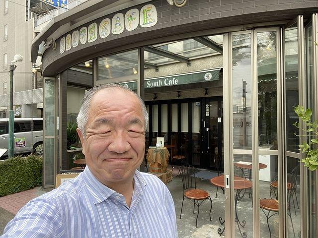 SOUTH CAFEの店頭で自撮りする鈴木義晴