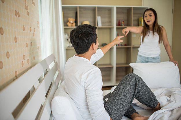 互いに指を差し合い口論する若い夫婦のイメージ画像