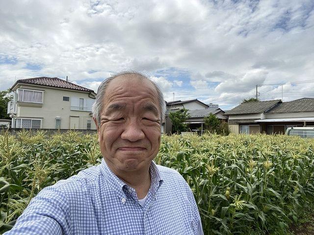 住吉町のとうもろこし畑をバックに写真を撮る鈴木義晴