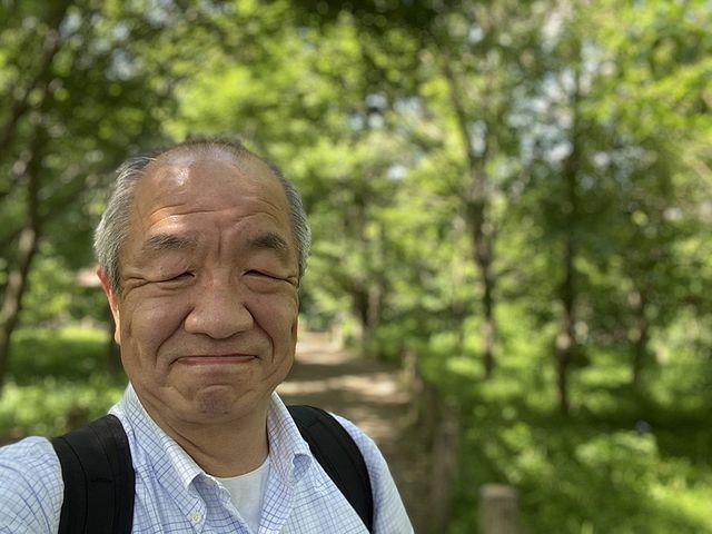 西原自然公園(2020.5.24)で樹々をバックに写真を撮る鈴木