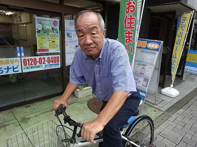 店頭で自転車に乗り出発する鈴木(スプラッシュ・代表)
