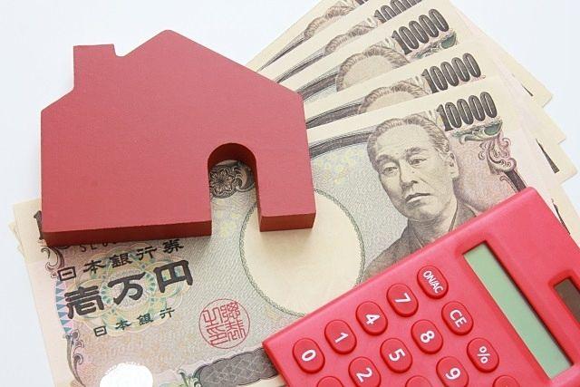 住宅ローンのイメージ画像(家のパズル・電卓・一万円札)