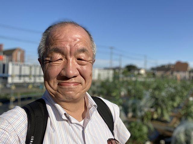 昭和の学び舎の畑を背景にする鈴木(2020.7.2)