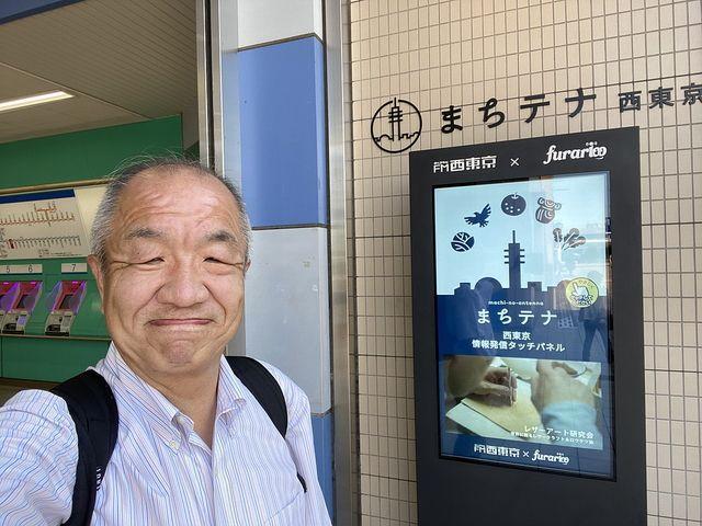 田無駅北口前のまちテナ西東京を背に自撮りする鈴木義晴