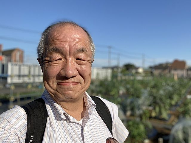 昭和の学び舎の畑で自撮りする鈴木義晴
