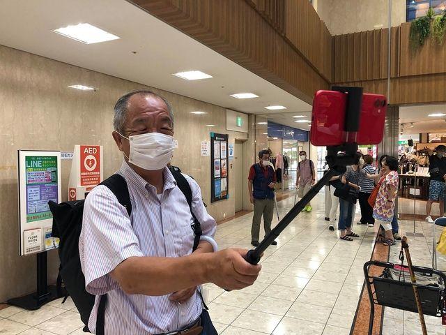 田無駅北口アスタ、センターコートにて取材する鈴木義晴の様子