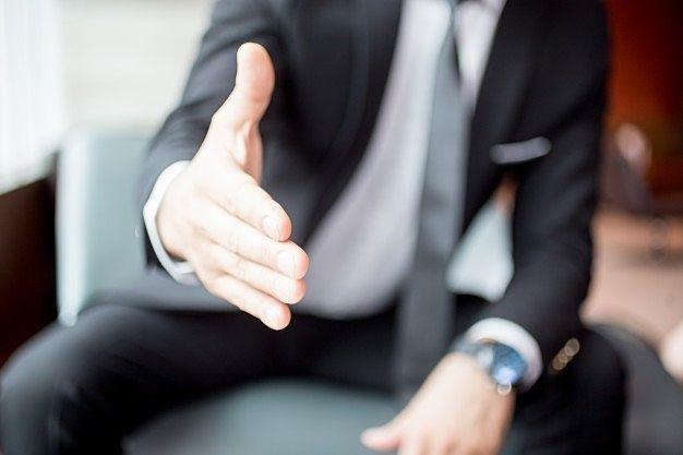 安心安全な取引のためには信用信頼のおける不動産会社を選択すること~握手を求める営業マン