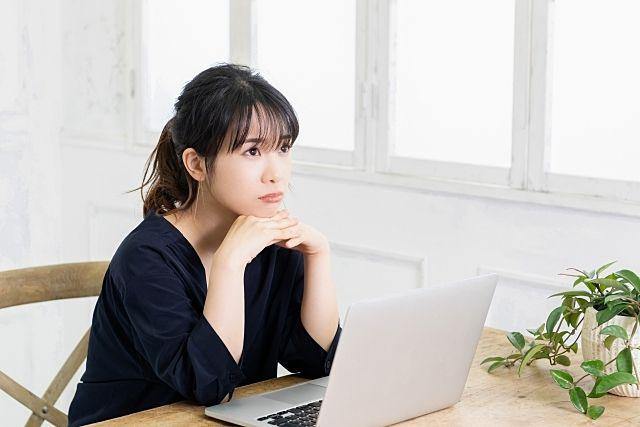 住まいを買うべきか‥パソコンを前に悩む女性