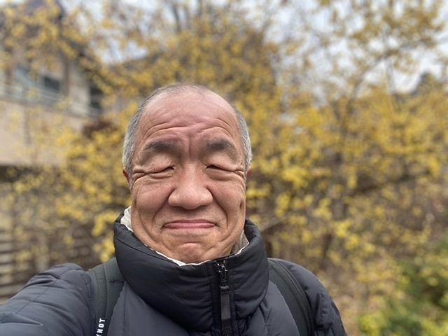 多摩自転車道の蝋梅をバックに自撮りする鈴木義晴
