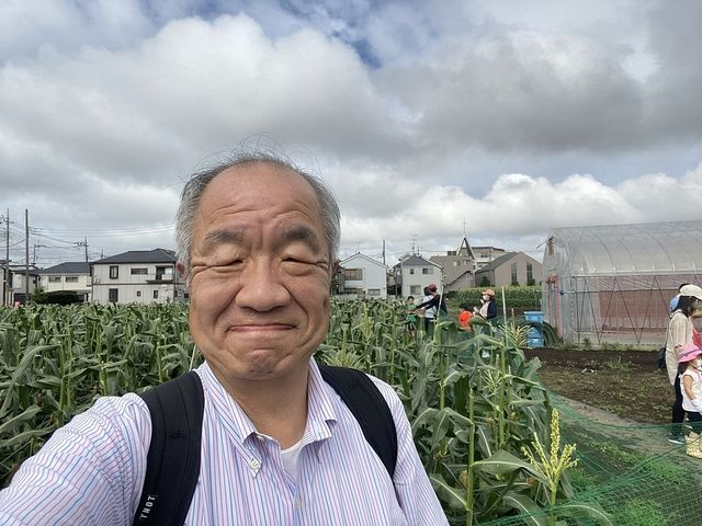 レイモンファームさんのトウモロコシ畑を背景に自撮りする鈴木義晴