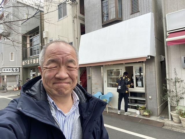 みかづきベーカリーの店頭をバックに自撮りする鈴木義晴(2021.3.5)スプラッシュ