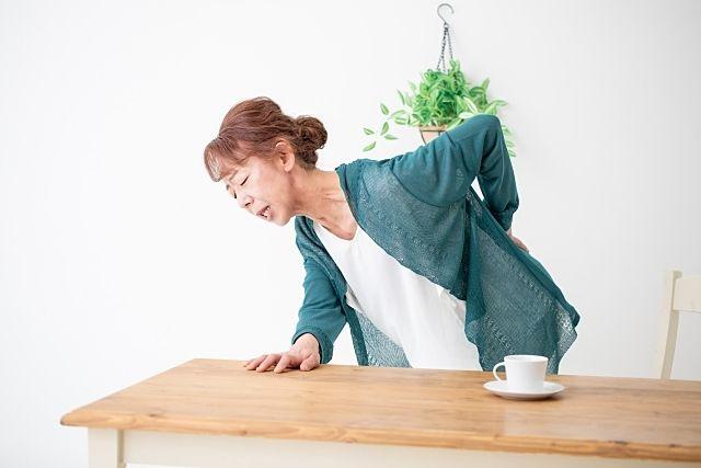 腰が痛くなり背中を叩く女性。もしかして骨粗しょう症かも(スプラッシュ)