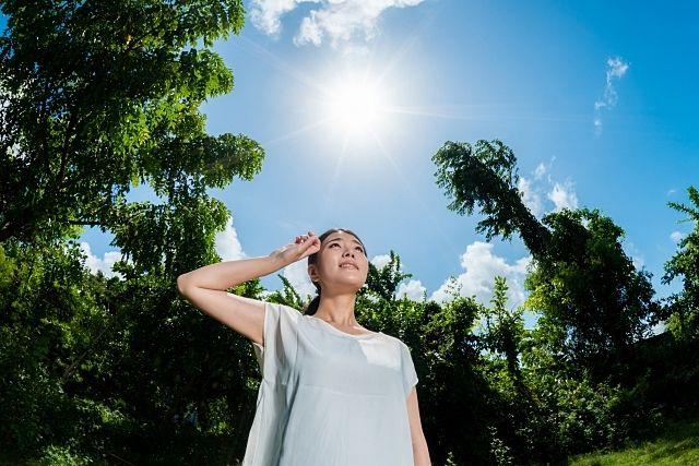 暑い日差しを手で遮る女性(スプラッシュ)