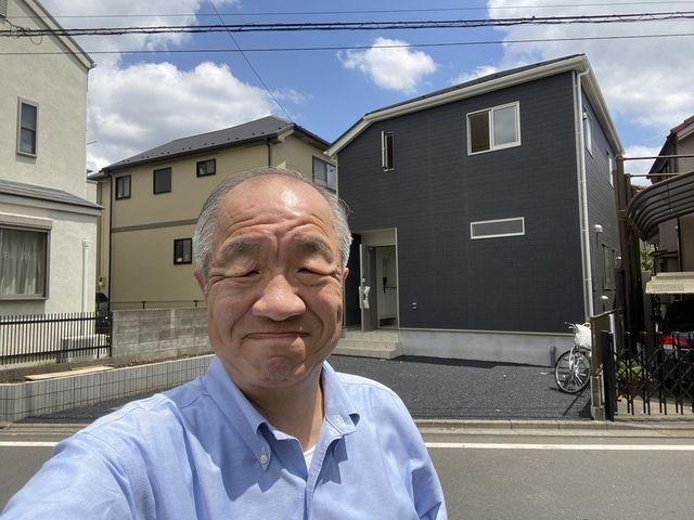 西東京市下保谷3丁目の完成した新築住宅をバックに自撮りする鈴木義晴
