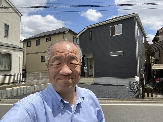西東京市下保谷3丁目の新築住宅を背景に写真を撮る鈴木義晴(2021.3.30)スプラッシュ