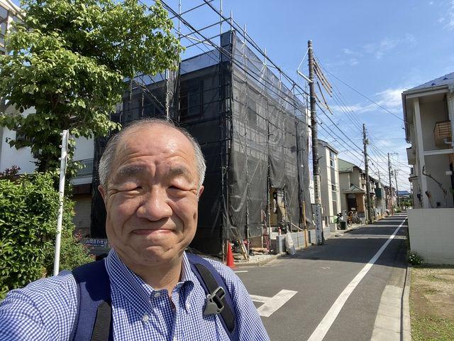 管理する西東京市泉町2丁目の新築住宅を背景に自撮りする鈴木義晴