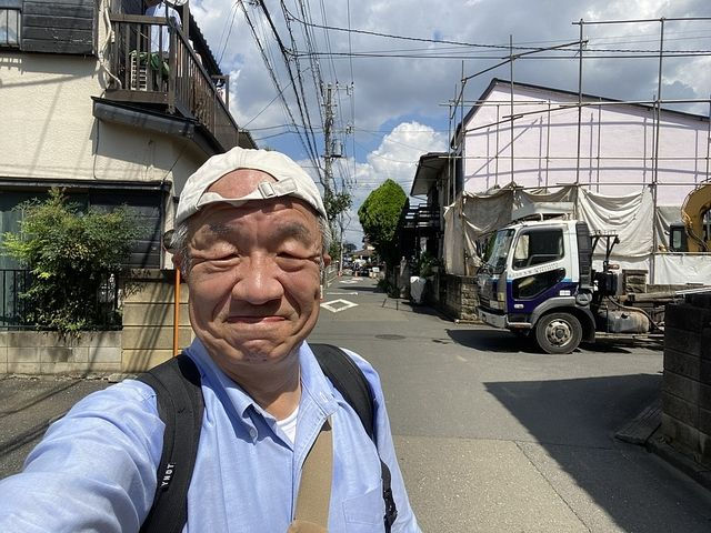 解体工事中の東久留米市八幡町3丁目の現地を背景に自撮りする鈴木義晴(2021.7.31)スプラッシュ