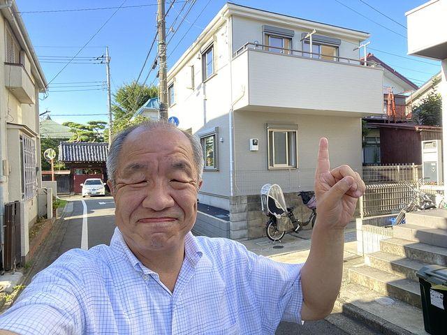 西東京市泉町2丁目の新築一戸建て背景に自撮りする鈴木義晴・スプラッシュ