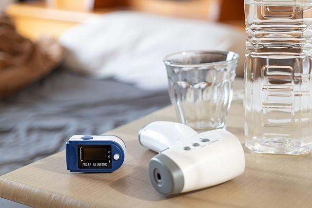 ベット脇のパルスオキシメーター、体温計、ペットボトルの水 スプラッシュ