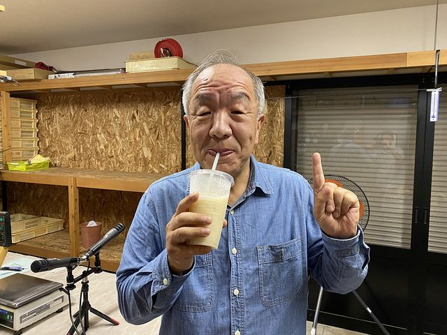 相田園さんの直売所バックヤードでなしのスムージーを飲む鈴木義晴(8.17)スプラッシュ