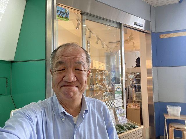 まちテナ西東京をバックに自撮りする鈴木義晴