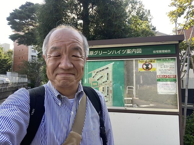 西原グリーンハイツの掲示板を背景に自撮りする鈴木義晴(2021.10.3)スプラッシュ