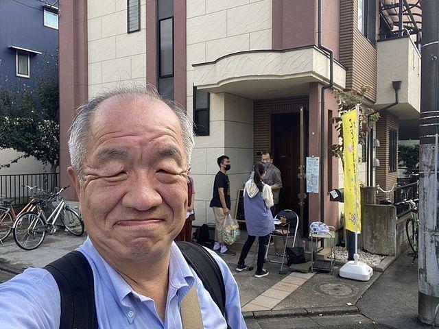 こども食堂げんきの開催されるお家を背景に自撮りする鈴木義晴(2021.10.10)