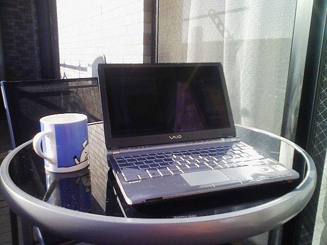 バルコニーのテーブルに置いたノートパソコンでリモートワークをしている様子