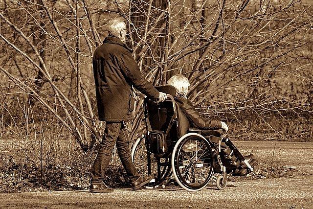 車椅子の妻を介護する夫