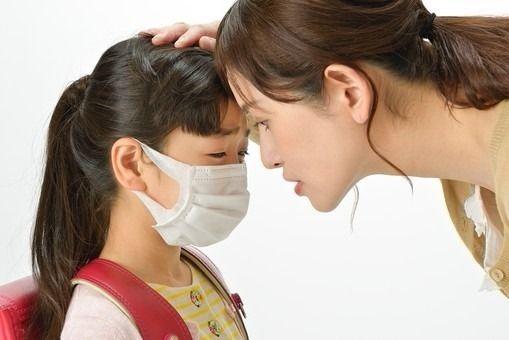 娘の額に手を当て熱を確認する母親